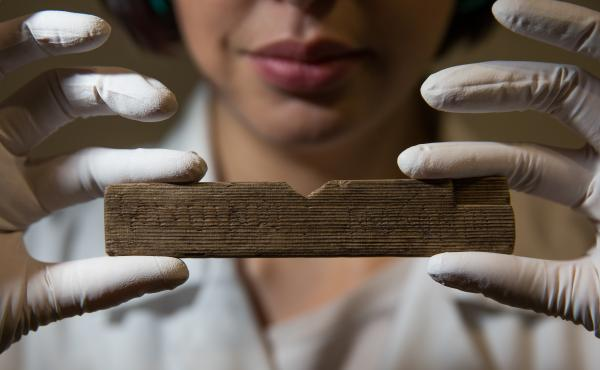 """Archaeological conservator Luisa Duarte holds a Roman waxed writing tablet at Bloomberg's London offices on Wednesday. This tablet contains the earliest written reference to London, dated A.D. 65-80; it reads """"Londinio Mogontio"""" --€"""" that is, """"in London"""