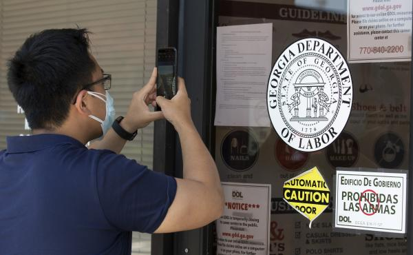 A man copies phone numbers posted on the locked doors of a Georgia Department of Labor office in in Norcross, Ga. Millennials are facing the second — or even third — economic downturn of their adult lives.