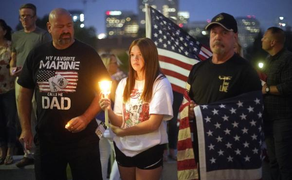 Sydney Robison, center, looks on during a vigil for U.S. Marines Staff Sgt. Taylor Hoover Sunday in Salt Lake City. Hoover was among the 13 U.S. troops killed in a suicide bombing at Kabul airport.