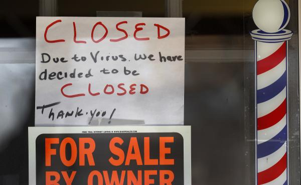 Signs are displayed in the window of a store in Grosse Pointe Woods, Mich. The Paycheck Protection Program, aimed at helping small businesses survive the coronavirus crisis, has been beset by problems.