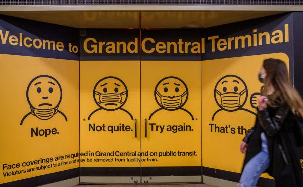 A woman walks past posters explaining mask requirements at Grand Central Terminal train station in New York City on Wednesday. Rules requiring masks on transit are unchanged by the Centers for Disease Control and Prevention's updated mask guidance for ful