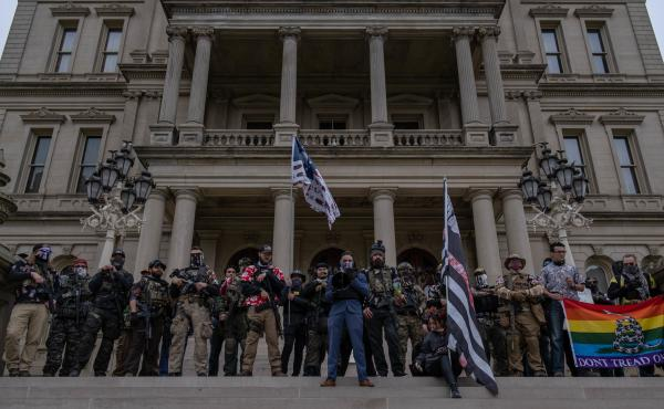 """Far-right extremist """"Boogaloo boys"""" stand on the steps of the capitol in Lansing, Mich., during a rally on Oct. 17. Michigan is one of five states with the highest risk of increased militia activity around the elections, according to a new report."""