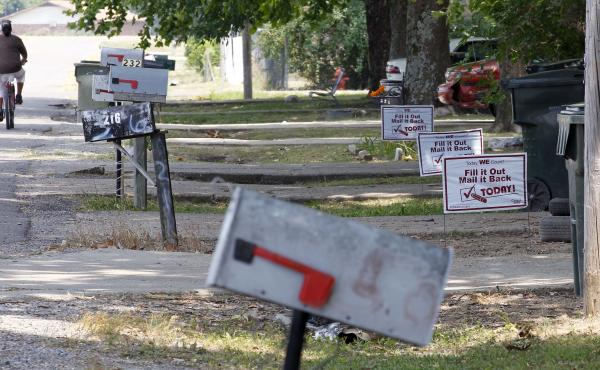 A bicyclist pedals past signs promoting the 2010 census outside homes in Rolling Fork, Miss., in 2010.