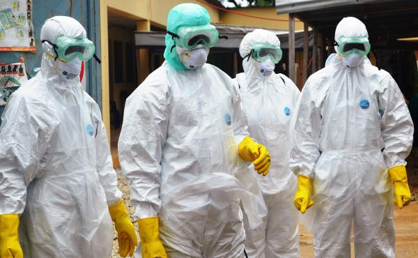 Red Cross health workers wearing protective suits in Conakry, Guinea, on Sunday.