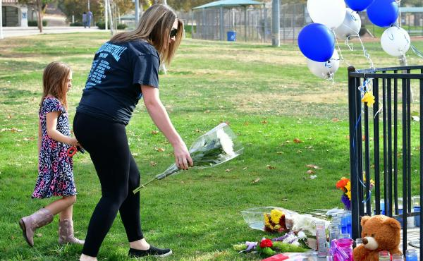 A woman and girl drop off flowers at a makeshift memorial in Central Park near Saugus High School in Santa Clarita, Calif., where a student shot five fellow teenagers Thursday.