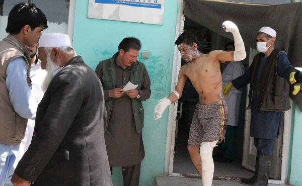 An injured boy is seen outside a hospital after two buses and a fuel tanker collided on a major highway in the Ghazni province of Afghanistan on Sunday.
