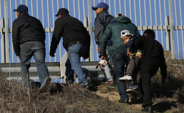 Migrants, one carrying a child, who plan to turn themselves over to U.S. border agents, walk up the embankment after climbing over a U.S. border wall from Playas de Tijuana, Mexico, last week. On Tuesday, members of the Hispanic Caucus called for improved