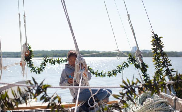 """Kala Tanaka marks """"stays"""" at the front of the canoe so they can go back in the same place after the mast is taken down to fit under the George Washington Bridge. The garlands of ti leaves, a Hawaiian tradition, were placed on the Hokule'a by well-wishers."""