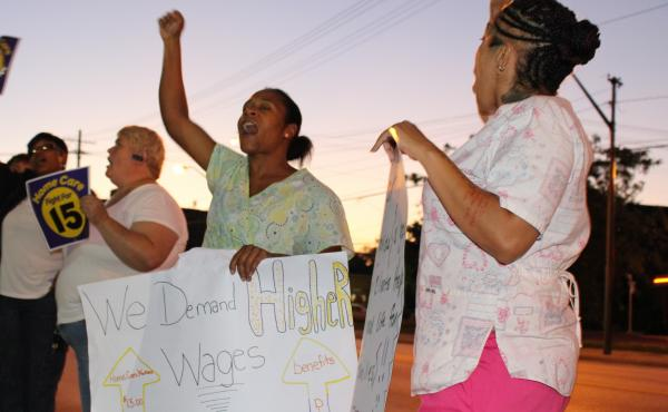 Home health care workers Jasmine Almodovar (far right) and Artheta Peters (center) take part in a Cleveland rally for higher pay on Sept. 4.