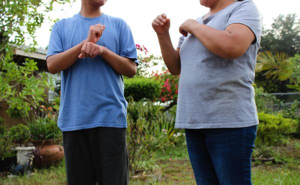 A Guatemalan teen asylum-seeker (left), who isn't able to hear or speak, signs with his mom in Florida. He was brusquely separated from her and held in a shelter for nearly three months, unable to readily communicate, according to a civil rights complaint