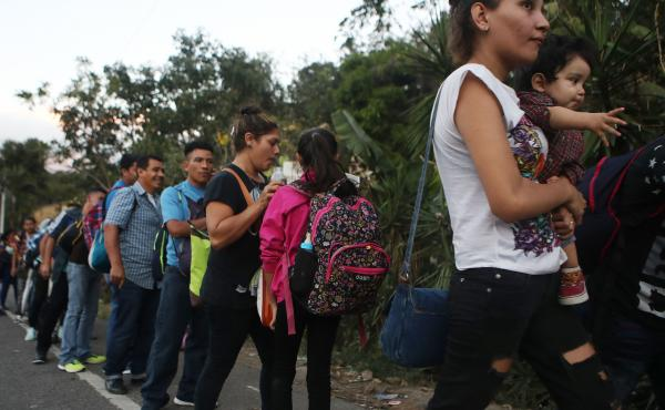 Honduran migrants wait in line to cross over the border checkpoint into Guatemala in Agua Caliente, Honduras. A new caravan of at least several hundred Hondurans has set off toward the United States on foot or in vehicles. Some have already crossed into G