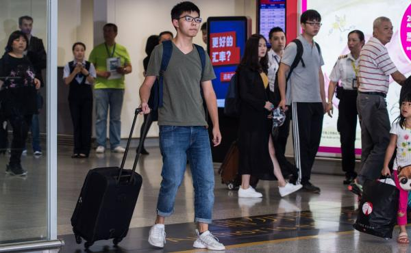 Pro-democracy activist Joshua Wong (center) arrives back in Hong Kong after being turned away from entering Bangkok by immigration officials and police.