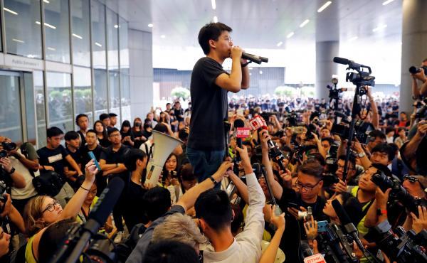 Pro-democracy activist Joshua Wong addresses the crowd outside Hong Kong's Legislative Council on Monday, during a demonstration demanding that Hong Kong's leaders step down and permanently withdraw an extradition bill.