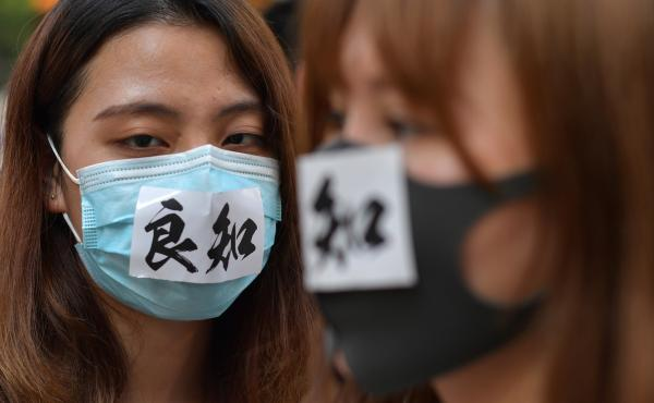 "A woman wearing a face mask with the characters meaning ""conscience"" takes part in a protest against a government ban on protesters wearing face masks in Hong Kong on Friday."