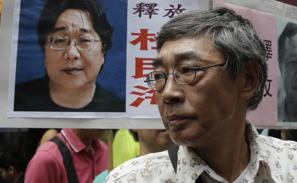 Freed Hong Kong bookseller Lam Wing-kee stands next to a placard with a picture of bookseller Gui Minhai, in front of his book store in Hong Kong in June 2016.