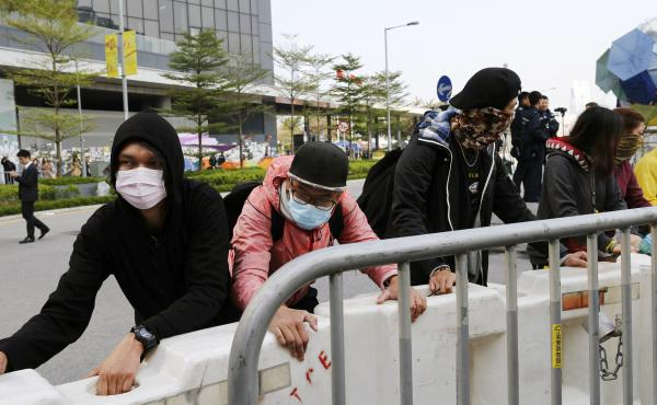Masked pro-democracy protesters move a barricade farther away from an office tower Tuesday in accordance to a court injunction to clear up part of the protest site, after the arrival of bailiffs outside the government headquarters in Hong Kong. Authoritie