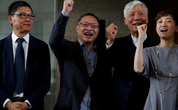 """Occupy Central founders Chan Kin-man, Benny Tai and Chu Yiu-ming chant slogans with fellow democracy advocate Tanya Chan, after the four and other activists were convicted of public nuisance crimes related to Hong Kong's """"Umbrella Movement"""" protests."""