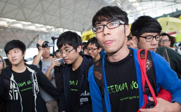 Federation of Students representatives Alex Chow Yong-kang (second left), Eason Chung Yiu-wa (second right) and Nathan Law Kwun-chung (right) talk to the media before trying to board a plane to Beijing on Saturday. They were told that Beijing authorities