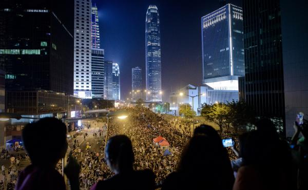 People watch as pro-democracy demonstrators gather for a Saturday night rally in Hong Kong. Hong Kong has been plunged into its most serious political crisis since its 1997 handover.