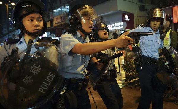 Policemen pull out their guns after a confrontation with demonstrators during a protest in Hong Kong, on Sunday. One officer fired a warning shot in the air — the first such incident in 11 weeks of protests.