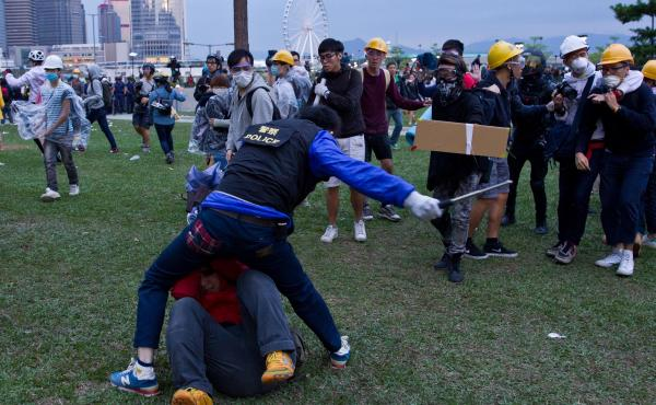 A policeman clashes with pro-democracy protesters during an operation to clear an occupied road near the government headquarters in the Admiralty district of Hong Kong early on Monday.