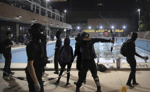Protesters practice firing bows and arrows on Thursday at Hong Kong Polytechnic University.