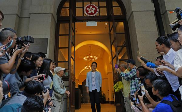 Pro-democracy activist Nathan Law (center) walks out from the Court of Final Appeal in Hong Kong on Tuesday.