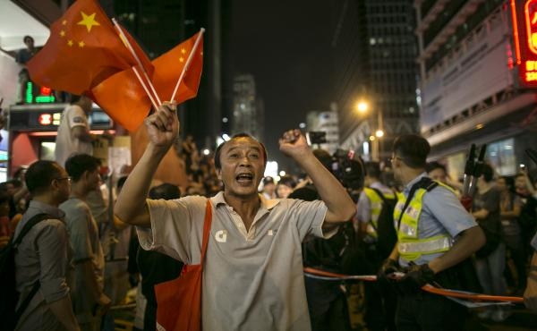 A resident of Kowloon holds the Chinese flags, screaming at the student democracy protesters to leave Mong Kok.