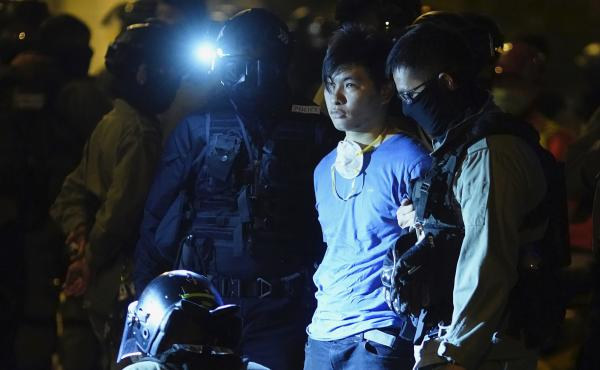 Riot police detain a protester on Tuesday near Hong Kong Polytechnic University, where  about 100 anti-government protesters remained holed up.