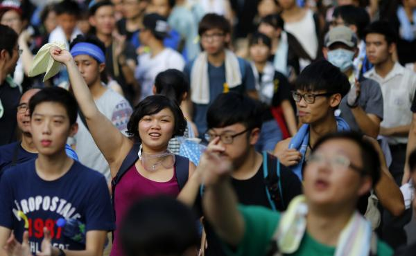 Protesters march as they block the main street to the financial Central district, outside the government headquarters in Hong Kong, on Monday. Protesters at times numbering in the tens of thousands have gathered to demand the right to choose the territory