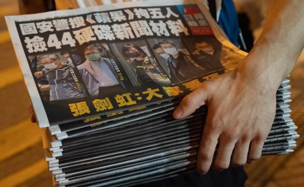 A man buys multiple copies of the latest Apple Daily newspaper in Hong Kong. Police raided the office of Apple Daily, the city's fierce pro-democracy newspaper, in an operation involving more than 200 officers. Secretary for Security John Lee said the com
