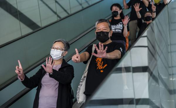 """Former lawmaker Cyd Ho (left) and pro-democracy activist Lee Cheuk-yan (center) gesture a protest slogan, """"Five demands, not one less,"""" as they leave West Kowloon court in Hong Kong on Thursday after being found guilty of organizing an unauthorized assemb"""