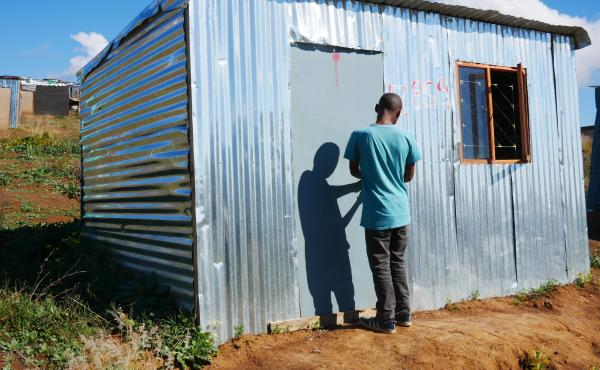 Ayanda stands in the doorway of a shack that he put up on illegally on privately owned farmland in Stellenbosch wine country. He says he grew tired of waiting for housing while living in Kayamandi township.