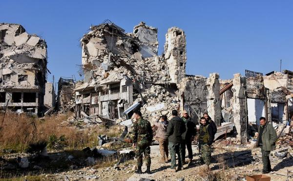 Syrian pro-government forces stand amidst the rubble in old Aleppo's Jdeideh neighborhood on Friday.