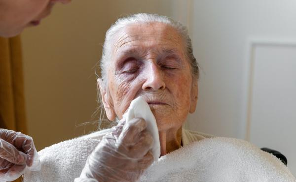 A certified nursing assistant wipes Neva Shinkle's face with chlorhexidine, an antimicrobial wash. Shinkle is a patient at Coventry Court Health Center, a nursing home in Anaheim, Calif., that is part of a multicenter research project aimed at stopping th