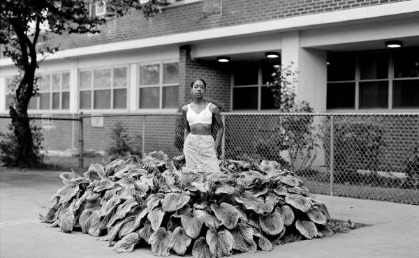 "Chanell Stone photographs places like overgrown lots and green spaces at public housing projects, often including herself in the frame. Above, ""In search of a certain Eden,"" 2019, Brooklyn."