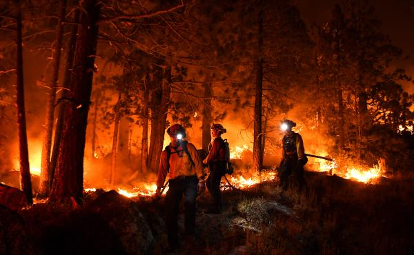 Firefighters battle the Caldor Fire this month along Highway 89 west of Lake Tahoe in California.