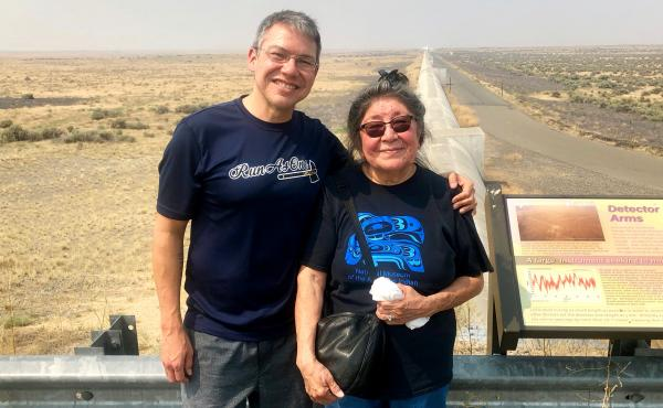 Scientist Corey Gray and his mother, Sharon Yellowfly, are pictured at one of the two massive detectors that make up the Laser Interferometer Gravitational-Wave Observatory. One facility, where Gray works, is in Washington state, and the other is in Louis
