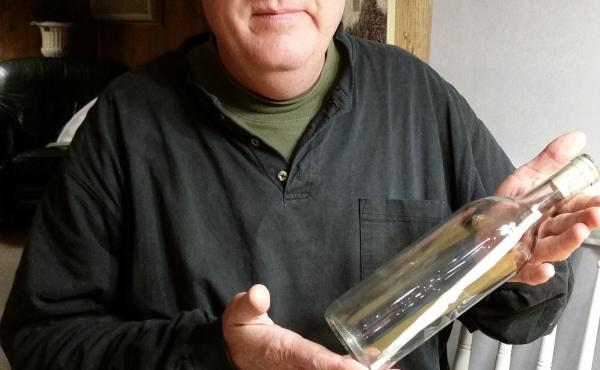 Ken Baker with a clear glass message bottles, though he favors green glass to send his notes. Inside, he writes about himself, mentions the bottle project and how far past bottles have gone and includes contact information.