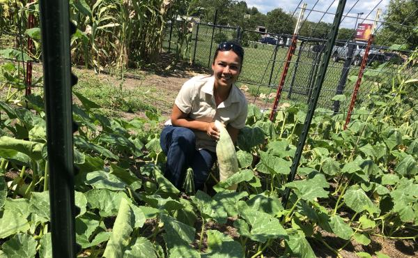 Cherokee Nation Cultural Biologist Feather Smith-Trevino holds an unripe Georgia Candy Roaster Squash at an educational garden in Tahlequah, Okla., where traditional native plants are grown.