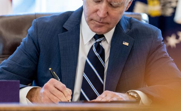 President Biden signs the American Rescue Plan in the Oval Office of the White House on March 11. Included in the plan is a monthly allowance for many American families that could be a potential financial-life-changer.