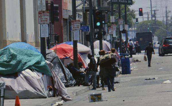 Tents housing homeless line a street down the street from LAPD Central Community Police Station in downtown Los Angeles on May 30, 2019. In this city, homeless encampments are sprouting up in underpasses, along streets and on sidewalks and inside parks.