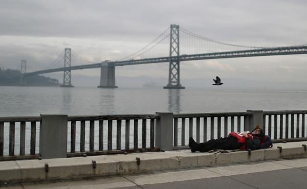SAN FRANCISCO, CALIFORNIA - DECEMBER 05: A homeless man sleeps on the sidewalk near the San Francisco–Oakland Bay Bridge on December 05, 2019 in San Francisco, California.