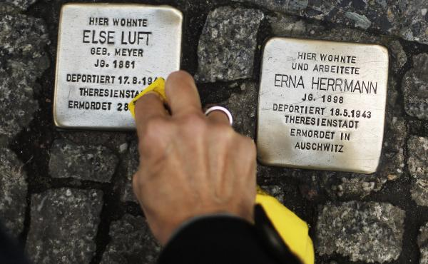 "A woman cleans a Stolperstein, or ""stumbling stone,"" placed in the sidewalk in front of houses where victims of the Holocaust lived before they were deported and killed by the Nazis."