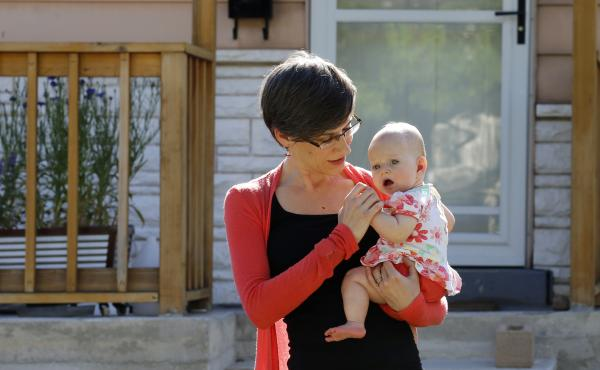 In this Friday, May 29, 2020, photo, Sara Adelman holds her daughter Amelia in Salt Lake City. Adelman is burning through her vacation time to help manage her current status as a working-from-home mom since her daughter's daycare closed due to the coronav