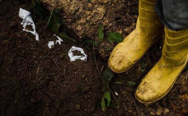 A burial team in Barkedu, Liberia, buries their protective clothing alongside the body of an Ebola victim. It's possible to catch the virus from clothing soiled by infected blood or other bodily fluids.