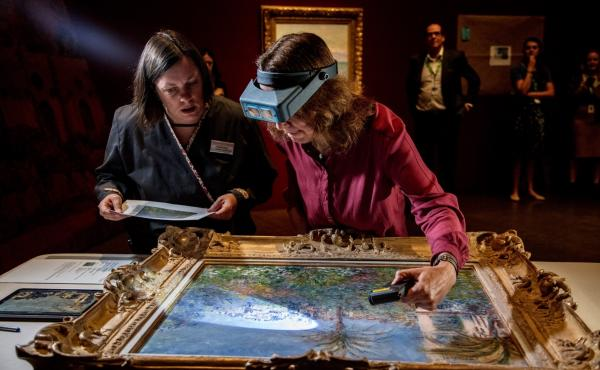 Conservator Felicitas Klein, right, traveled from Germany with Villas at Bordighera, an 1884 painting by Claude Monet. She inspects the painting at the Denver Art Museum, along with senior paintings conservator Pamela Skiles.