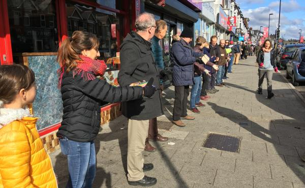 People pass books down a chain to help the bookstore October Books move to a new location on Sunday in Southampton, England.