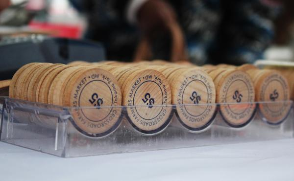 These wooden tokens are handed out to shoppers who use SNAP benefits to purchase fresh produce at the Crossroads Farmers Market near Takoma Park, Md. Customers receive tokens worth twice the amount of money withdrawn from their SNAP benefits card — in o