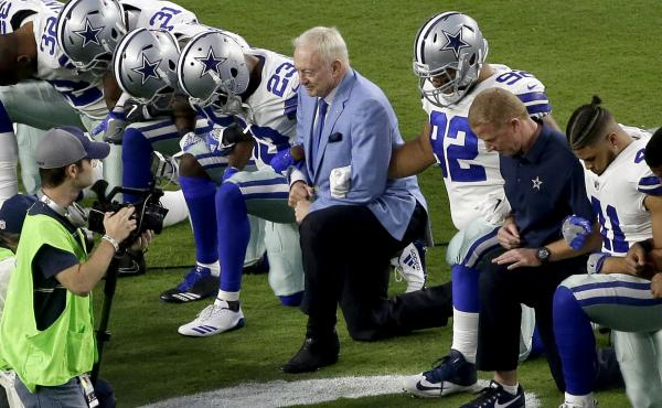 The Dallas Cowboys, led by owner Jerry Jones, center, take a knee prior to the national anthem Monday night in Glendale, Ariz., ahead of the team's game against the Arizona Cardinals.